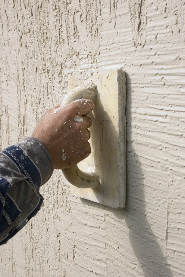 oviedo stucco repair pro putting final texture using hand tool on stucco wall.